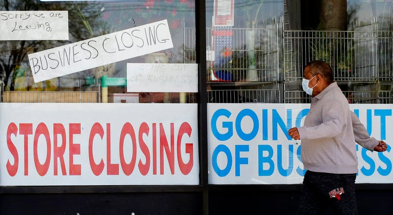 FILE - In this May 21, 2020 file photo, a man looks at signs of a closed store due to COVID-19 in Niles, Ill.