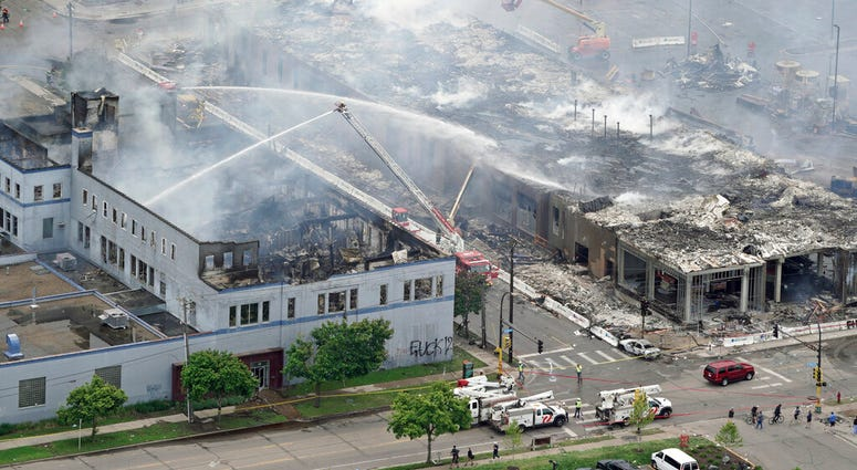 Firefighters work on an apartment building under construction, Thursday, May 28, 2020, tentatively known as Midtown Corner, left, after it was burned to the ground in Minneapolis, Minn.