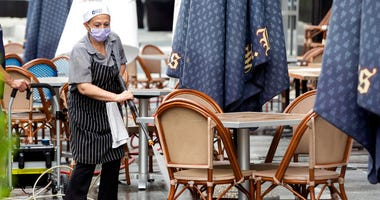 In this May 27, 2020, photo, a worker at Brasserie Beck, a restaurant along K Street in downtown Washington, power washes the outdoor seating area.