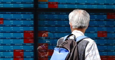 A man looks at an electronic stock board showing Japan's Nikkei 225 index at a securities firm in Tokyo Friday, May 29, 2020. Shares fell Friday in Asia after Wall Street's rally petered out amid worries about flaring U.S.-China tensions.