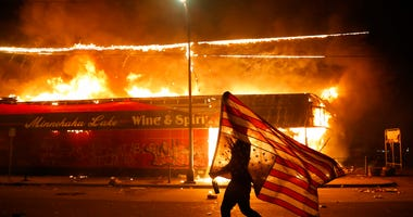 A protester carries a U.S. flag upside, a sign of distress, next to a burning building Thursday, May 28, 2020, in Minneapolis. (AP Photo/Julio Cortez)