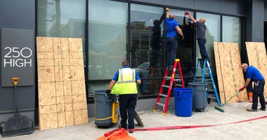 Workers repair smashed windows at a building south of downtown on Friday, May 29, 2020, in Columbus, Ohio. Multiple downtown storefronts had their windows smashed and some businesses were looted early Friday.