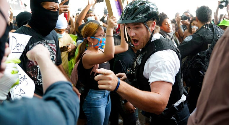 Demonstrators argue with uniformed U.S Secret Service police officers during a protest about the death of George Floyd, a black man who died in police custody in Minneapolis, Friday, May 29, 2020, in Washington.