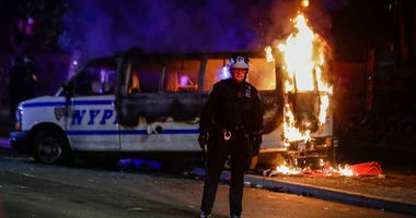 A police officer watches a crowd as a police vehicle burns near Fort Greene Park in the Brooklyn borough of New York after protesters rallied outside Barclays Center over the death of George Floyd, a black man who died Memorial Day while in police custody
