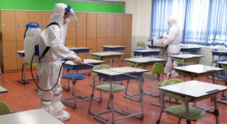 Workers wearing protective gear disinfect as a precaution against the new coronavirus in a class at a high school in Busan, South Korea, Saturday, May 30, 2020.