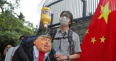 Pro-China supporters hold the effigy of U.S. President Donald Trump and Chinese national flag outside the U.S. Consulate during a protest in Hong Kong, Saturday, May 30, 2020.