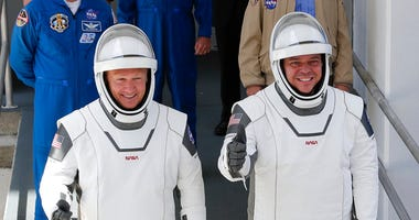 NASA astronauts Douglas Hurley, left, and Robert Behnken walk out of the Neil A. Armstrong Operations and Checkout Building on their way to Pad 39-A, at the Kennedy Space Center in Cape Canaveral, Fla., Saturday, May 30, 2020.