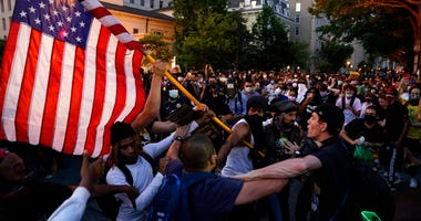 Demonstrators clash as people gather to protest the death of George Floyd, Saturday, May 30, 2020, near the White House in Washington.