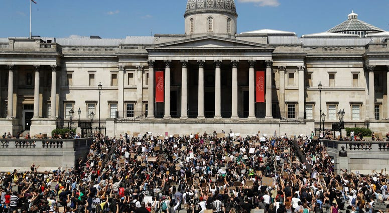 People, some of them kneeling gather in Trafalgar Square in central London on Sunday, May 31, 2020 to protest against the recent killing of George Floyd by police officers in Minneapolis that has led to protests across the US.