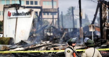 San Diego County sheriff officers stand guard in front of a burning bank building after a protest over the death of George Floyd, Sunday, May 31, 2020, in La Mesa, Calif.