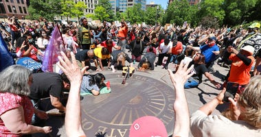 """Members of the Shiloh Christian Center pray, sing and speak in tounges on the """"With God All Things Are Possible"""" seal on the west lawn of the Ohio Statehouse as protesters gather at the Ohio Statehouse for a peaceful Sunday, May 31, 2020 protest over the"""