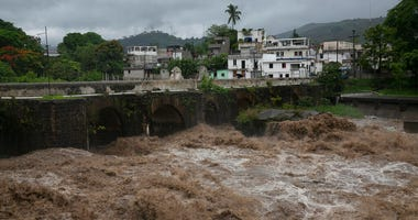 The swollen Los Esclavos River flows violently during tropical storm Amanda in Cuilapa, eastern Guatemala, Sunday, May 31, 2020.
