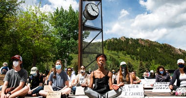Jenelle Figgins, center, leads a moment of silent meditation before protesters march through the streets of Aspen, Colo., Sunday, May 31, 2020, to demonstrate against the death of George Floyd.
