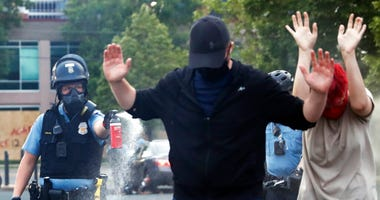 An officer points pepper spray towards people after curfew on Sunday, May 31, 2020 in Minneapolis.
