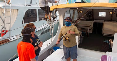 In this photo provided by the Florida Keys News Bureau, Captain Glenn Miller climbs to the bridge on his sport fishing boat GonFishin V; while mate Josh Rabon, right, explains to his guests what to expect during the planned day of fishing off the Florida