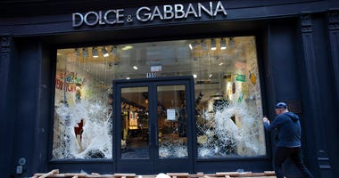 A passerby photographs a smashed Dolce and Gabbana store window in the SoHo neighbourhood of New York, Monday, June 1, 2020.