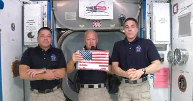In this image taken from NASA video on Monday, June 1, 2020, NASA astronauts Robert L. Behnken, left, and Chris Cassidy right, listen as commander Douglas Hurley speaks about retrieving the American flag left behind at the International Space Station near