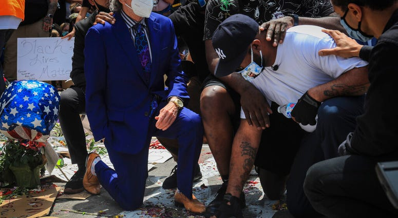 An emotional Terrence Floyd, second from right, is comforted as he touch the spot at the intersection of 38th Street and Chicago Avenue, Minneapolis, Minn., where his brother George Floyd, encountered police and died while in their custody, Monday, June 1