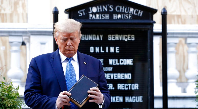 President Donald Trump holds a Bible as he visits outside St. John's Church across Lafayette Park from the White House Monday, June 1, 2020, in Washington. Part of the church was set on fire during protests on Sunday night.