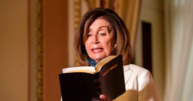 House Speaker Nancy Pelosi of Calif., reads from the Bible, as she reacts to President Donald Trump during a news conference at the U.S. Capitol in Washington, Tuesday, June 2, 2020.