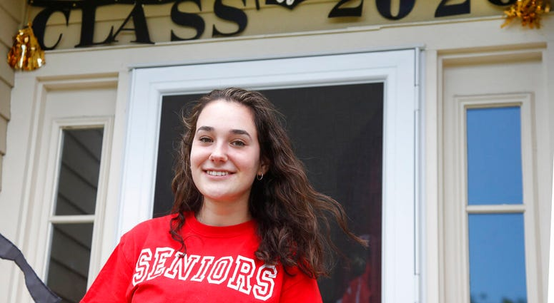In this June 1, 2020 photo, high school graduate Lizzie Quinlivan poses at her home in Hingham, Mass.