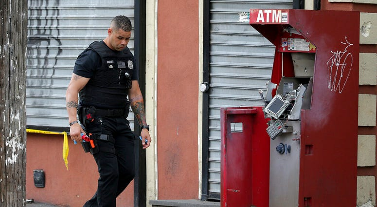 A member of the Philadelphia bomb squad surveys the scene after an ATM machine was blown-up at 2207 N. 2nd Street in Philadelphia, Tuesday, June 2, 2020.