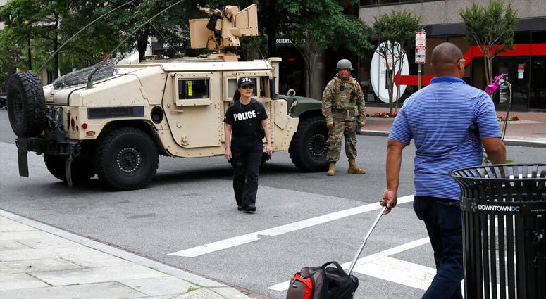 A man walks through an intersection blocked by a military humvee from DC National Guard and a DEA police officer as demonstrators gather to protest the death of George Floyd, Tuesday, June 2, 2020, in Washington.