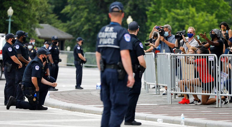 Members of the capitol police kneel as demonstrators gather to protest the death of George Floyd, Wednesday, June 3, 2020, outside the U.S. Capitol in Washington.