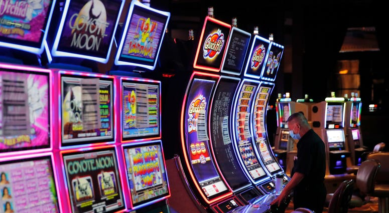 FILE - In this May 21, 2020, file photo, a worker looks over an electronic slot machine as chairs have been removed from some machines to maintain social distancing between players at a closed Caesars Palace hotel and casino in Las Vegas.