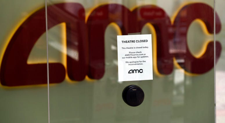 FILE - In this April 29, 2020 file photo, a message on the ticket window at the AMC Burbank 16 movie theaters complex informs potential customers that it is currently closed in Burbank, Calif.