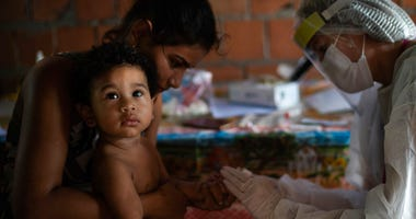A health worker tests 1-year-old Nicolas for COVID-19 at his home after a family member fell ill in Manacapuru, Amazonas state, Brazil, Wednesday, June 3, 2020.