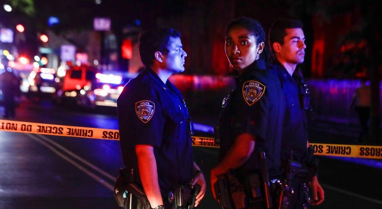 New York City police stand on a street early Thursday, June 4, 2020, in the Brooklyn borough of New York, after a police officer was shot. The police department says an officer has been shot in Brooklyn.