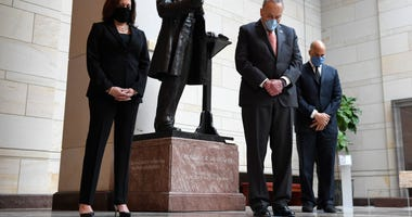 Standing near a statue of Frederick Douglass, Sen. Kamala Harris, D-Calif., left, Senate Minority Leader Sen. Chuck Schumer of N.Y., center, and Sen. Cory Booker, D-N.J.,, right, pause during a prayer Capitol Hill in Washington, Thursday, June 4, 2020, du