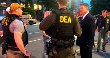 In this Wednesday, June 3, 2020, photo Acting Drug Enforcement Administrator Timothy Shea, right, visits with DEA agents at a checkpoint in Washington.