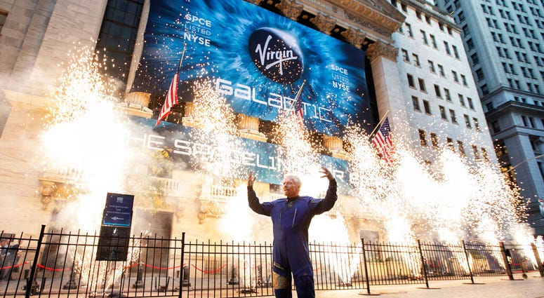 FILE - In this Monday, Oct. 28, 2019 file photo, Sir Richard Branson, founder of Virgin Galactic, poses for a photo outside the New York Stock Exchange as fireworks are exploded before his company's IPO.