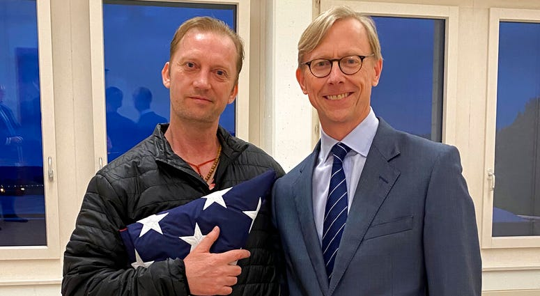In this image provided by the U.S. State Department, Michael White holds an American flag as he poses for a photo Thursday, June 4, 2020, with U.S.