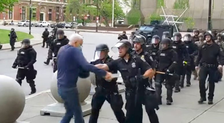 In this image from video provided by WBFO, a Buffalo police officer appears to shove a man who walked up to police Thursday, June 4, 2020, in Buffalo, N.Y. Video from WBFO shows the man appearing to hit his head on the pavement, with blood leaking out as