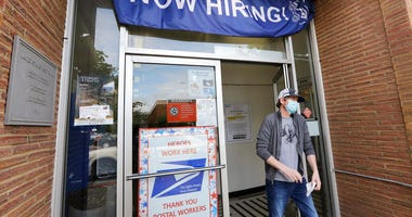 In this photo taken Thursday, June 4, 2020, a customer walks out of a U.S. Post Office branch and under a banner advertising a job opening, in Seattle.