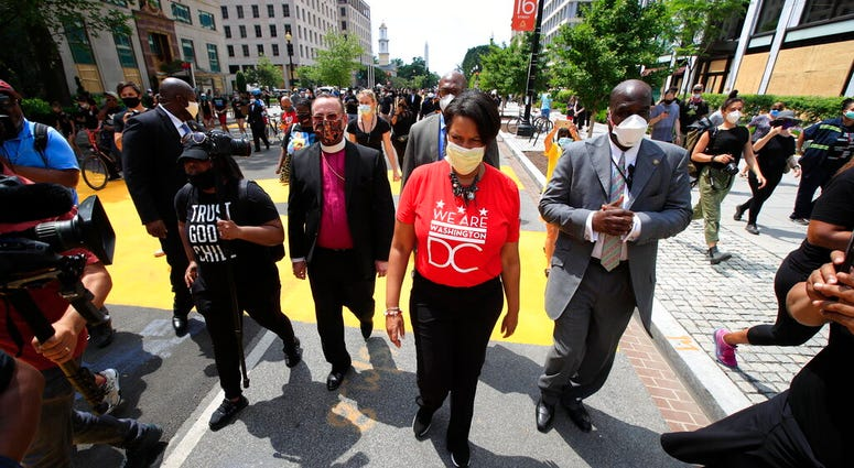 District of Columbia Mayor Muriel Bowser walks on the street leading to the White House after the words Black Lives Matter were painted in enormous bright yellow letters on the street by city workers and activists Friday, June 5, 2020, in Washington.