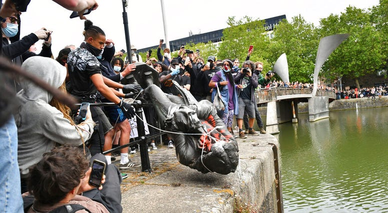Protesters throw a statue of slave trader Edward Colston into Bristol harbour, during a Black Lives Matter protest rally, in Bristol, England, Sunday June 7, 2020, in response to the recent killing of George Floyd by police officers in Minneapolis, USA, t