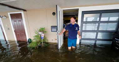 Rudy Horvath walks out of his home, a boathouse in the West End section of New Orleans, as it takes on water a from storm surge in Lake Pontchartrain in advance of Tropical Storm Cristobal, Sunday, June 7, 2020.