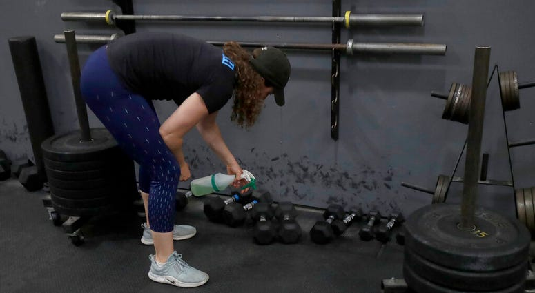 FILE - In a Friday, April 24, 2020 file photo, Alexis Garrod, CrossFit Potrero Hill partner and head coach, cleans off weight training equipment in an empty gym, which closed for shelter in place orders over COVID-19 concerns, in San Francisco.