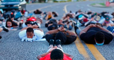 Six-year-old Blue Scott, of Florissant, Mo.,assumes a prone position on Sunday, June 7, 2020, as he participates with about 100 protesters in a die-in in the middle of Lindbergh Boulevard in front of the Florissant Police Station in Florissant, Mo.