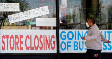 FILE - In this May 21, 2020 file photo, a man looks at signs of a closed store due to COVID-19 in Niles, Ill.   (AP Photo/Nam Y. Huh, File)