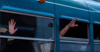 FILE - In this May 4, 2020, file photo, Guatemalans deported from the United States, wave from a bus after arriving at La Aurora airport in Guatemala City.