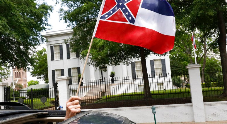 """In this April 25, 2020 photograph, a small Mississippi state flag is held by a participant during a drive-by """"re-open Mississippi"""" protest past the Governor's Mansion, in the background, in Jackson, Miss."""