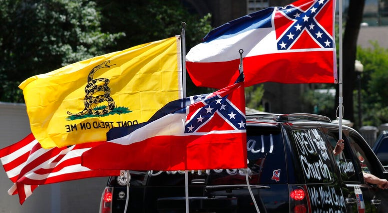 "In this April 25, 2020 photo, Mississippi state flags are positioned on a vehicle amid an arrangement with the American flag and a Gadsden flag during a drive-by ""re-open Mississippi"" protest past the Governor's Mansion, in Jackson, Miss."