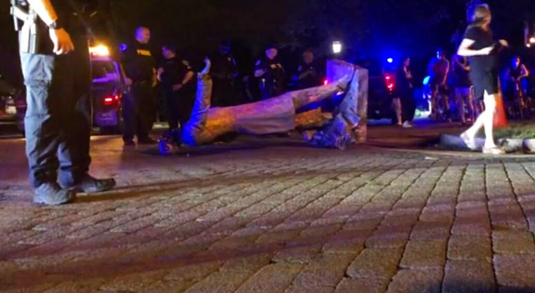 In this image from video, police stand near a toppled statue of Jefferson Davis on Wednesday night, June 10, 2020, in Richmond, Va. Protesters tore down the statue of Confederate President Davis along Monument Avenue.