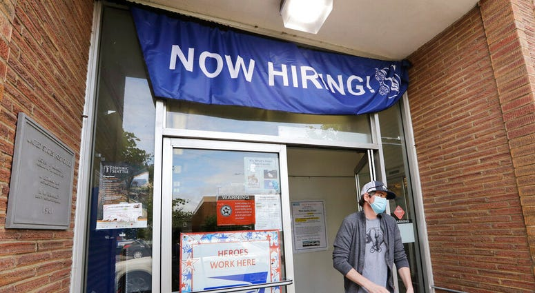 FILE - In this June 4, 2020 photo, a customer walks out of a U.S. Post Office branch and under a banner advertising a job opening, in Seattle.