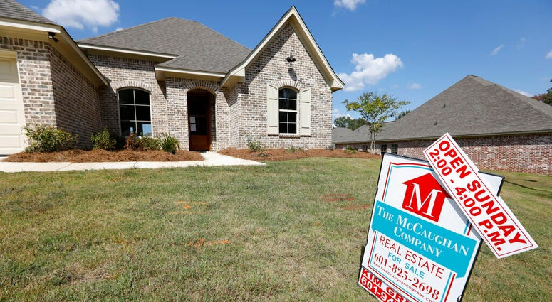 FILE - In this Sept. 25, 2019 file photo, a sign promoting an open house sits atop a realty company's lawn sign in Brandon Miss.